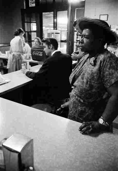 Segregated Lunch Counter. While waiting for a train to take him from Chattanooga to Memphis, Elvis sits at the lunch counter to have some breakfast. The woman standing in the foreground was waiting for a sandwich that she had ordered; she was not allowed to sit at the counter. Railroad station, Chattanooga, Tenn., July 4, 1956