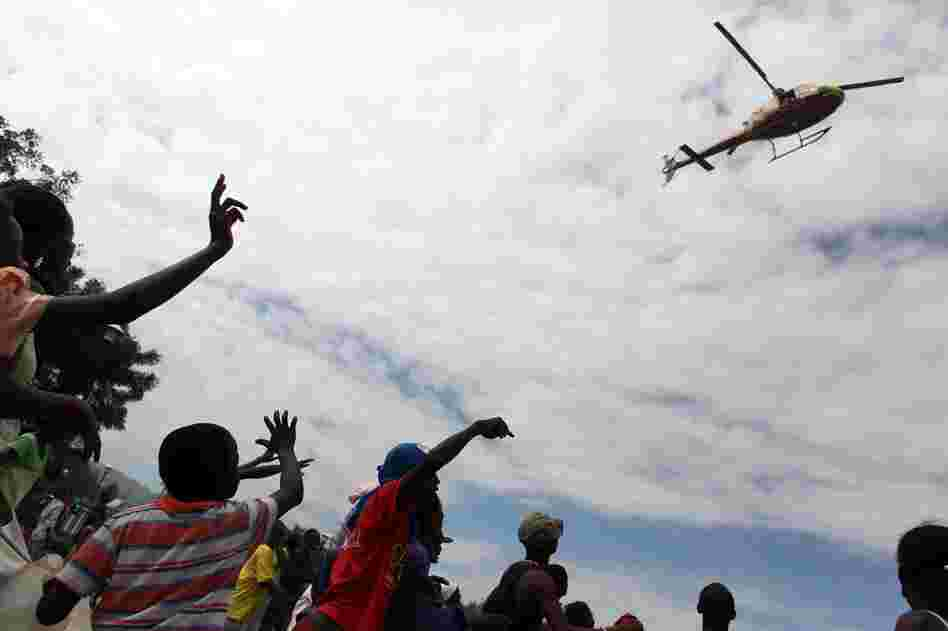 People wave at a helicopter in the center of Port-au-Prince. Aid efforts are slow to reach the Haitian capital.