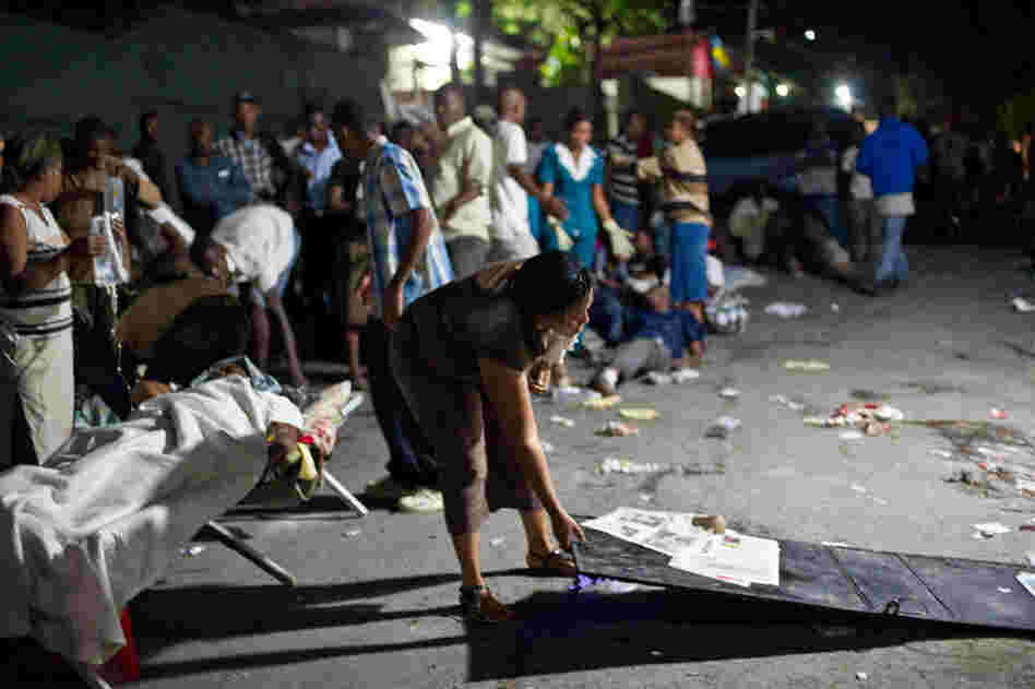 A woman prepares a bed in the street Tuesday night after the quake.
