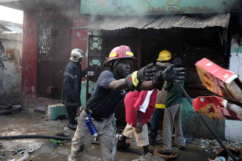 Fireman attempt to put out a blaze in Port-au-Prince Thursday.
