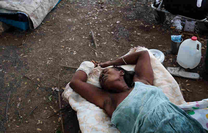 A woman who lost a hand lies on the ground outside a makeshift recovery ward in Port-au-Prince Friday.