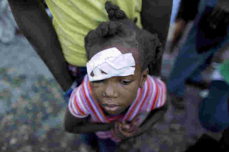 An injured child waits for medical attention near a damaged hospital in Carrefour, on the outskirts of Port-au-Prince, Friday.