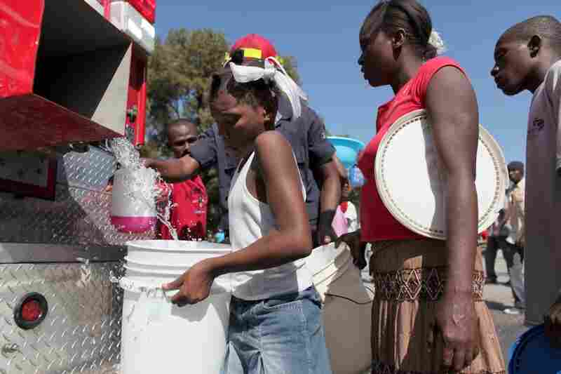 People line up to receive water, an in-demand commodity, from a firetruck in Port-au-Prince.