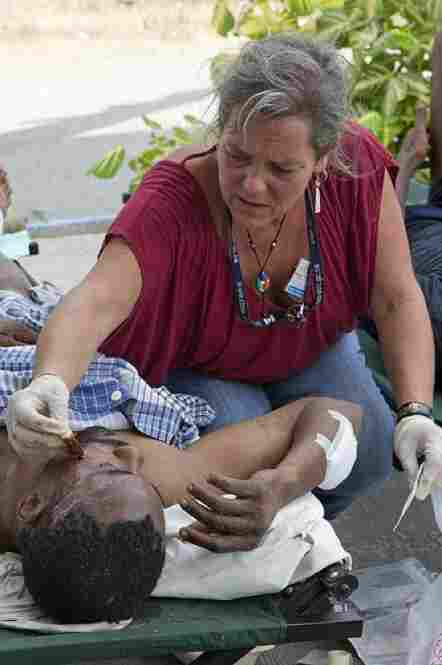 A staff member from the U.N. Stabilization Mission in Haiti, or MINUSTAH, treats an injured man.