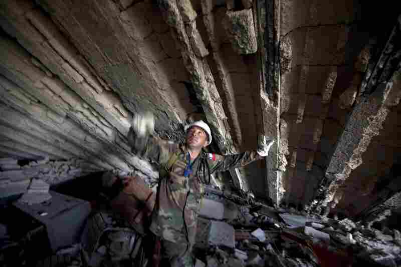 A U.N. peacekeeper from Chile works in the rubble of the Montana Hotel.