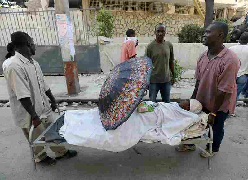 Men carry an injured relative in Port-au-Prince. The Haitian Red Cross estimates that more than 50,000 people may have been killed in the earthquake.