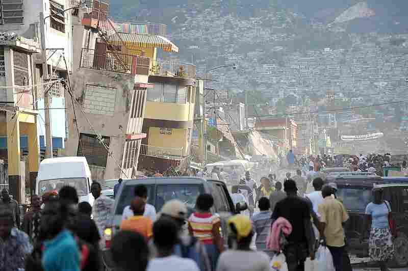 Haitians walk though streets filled with rubble and bodies.