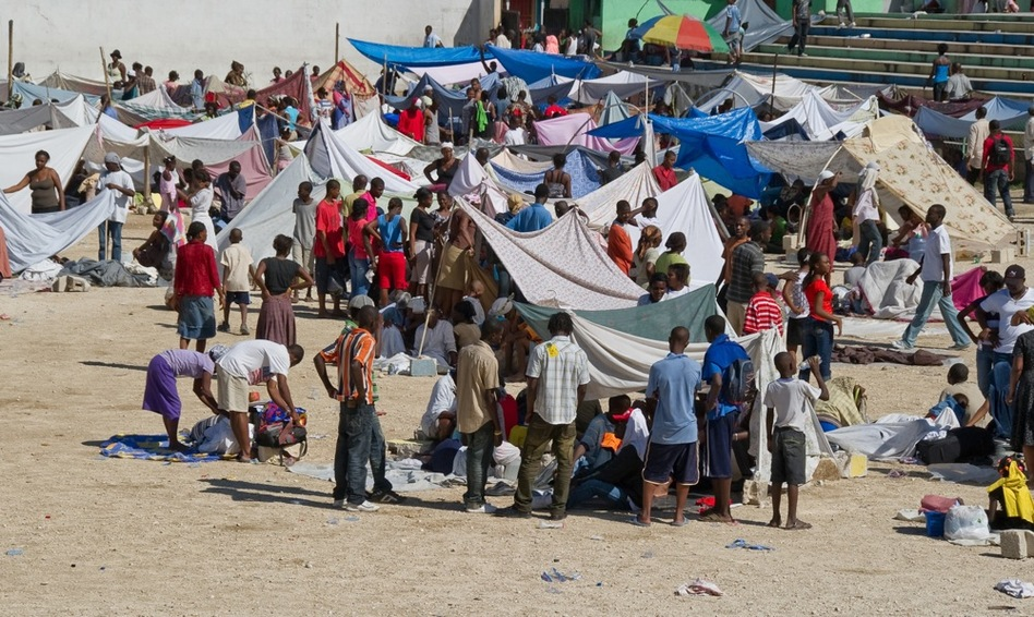 Displaced people create makeshift shelters out of tarps and sheets.