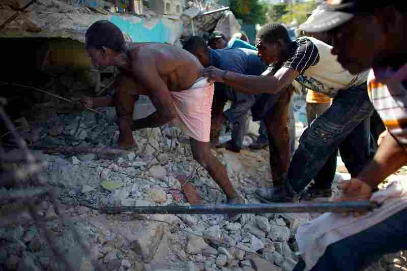 Haitian men dig for a relative in a collapsed house outside of the capital.