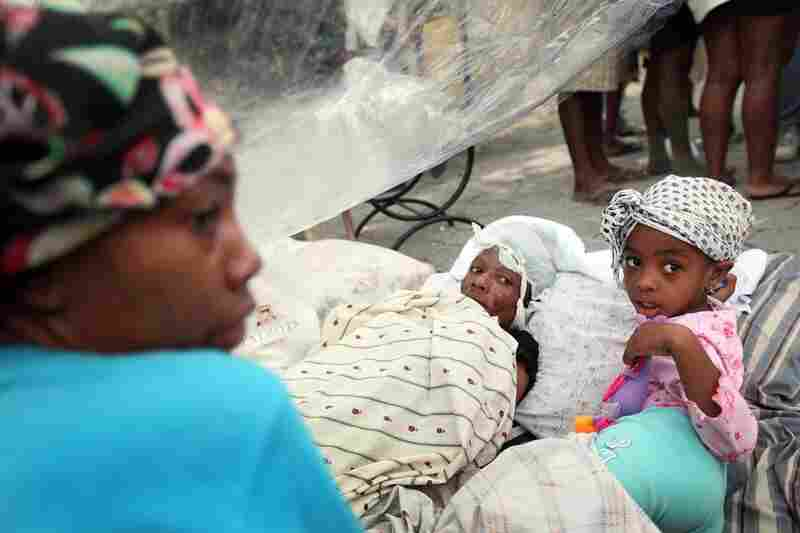 Injured people rest in the streets of Port-au-Prince Thursday, two days after the devastating 7.0 quake.