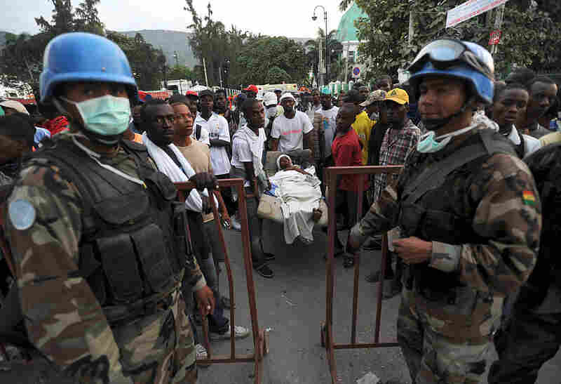 Bolivian U.N. Blue Helmet soldiers stand guard at an aid center in Port-au-Prince as a group of Haitians carries a victim.