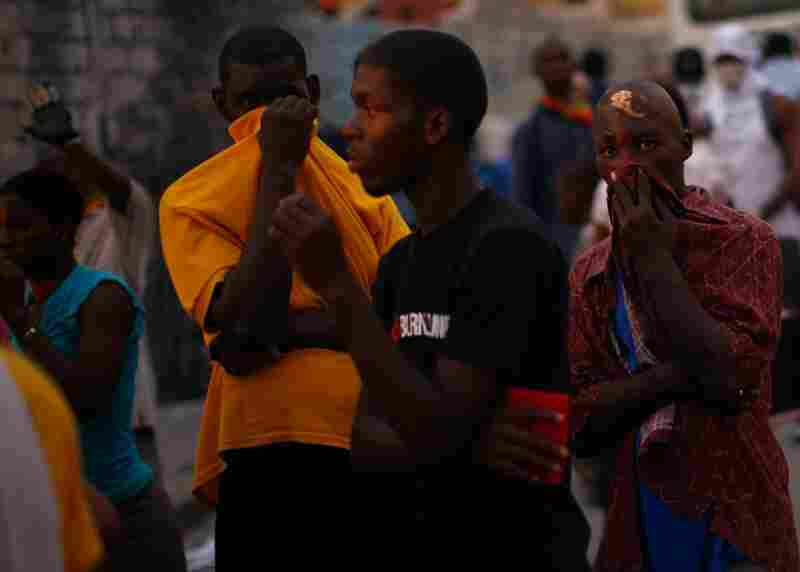 Haitian men cover their faces from the stench of decay as bodies are removed from the streets of Port-au-Prince.