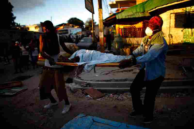 Haitian men carry the body of a child to a dump truck near downtown Port-au-Prince on Thursday.