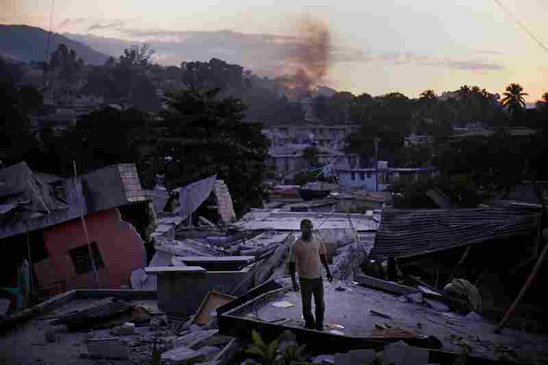 A man stands on a rooftop yelling out for any sign of his missing relatives Friday in a devastated hillside neighborhood near downtown Port-au-Prince.