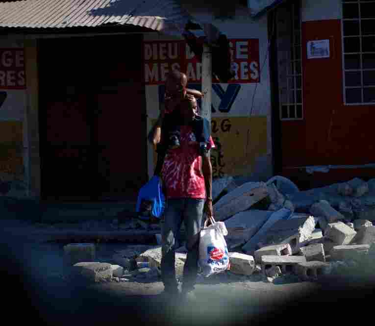 A man stands with his child on his shoulders outside a collapsed building. In what has long been the Western Hemisphere's poorest nation, shock was giving way to despair.