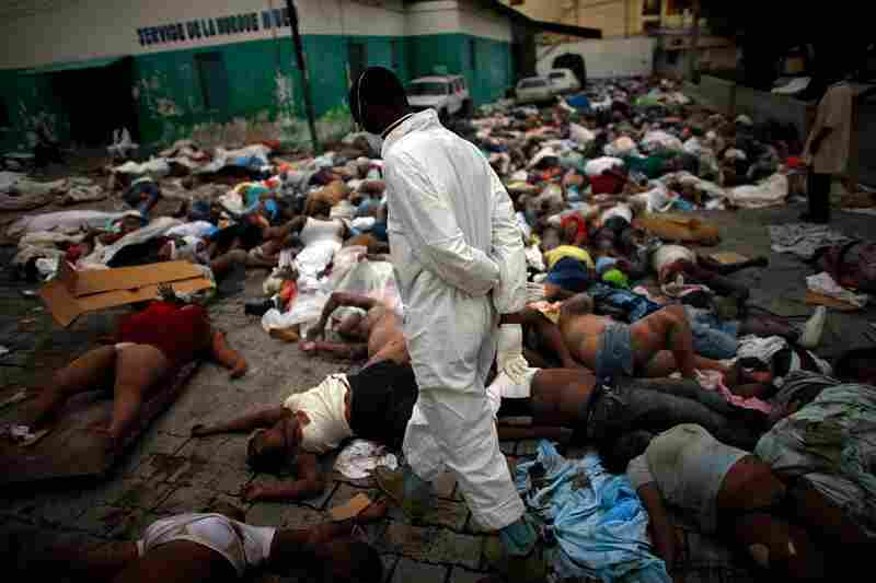 Workers are trying to deal with the thousands of bodies piling up at the central morgue at the National Hospital in Port-au-Prince.