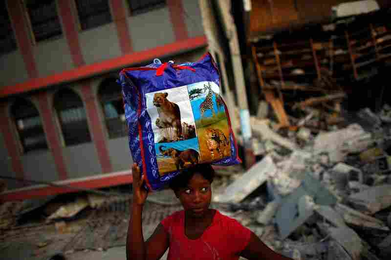 Across Port-au-Prince Haitians are scrambling to salvage what they can. A woman carries a bag of clothing recovered from her apartment.