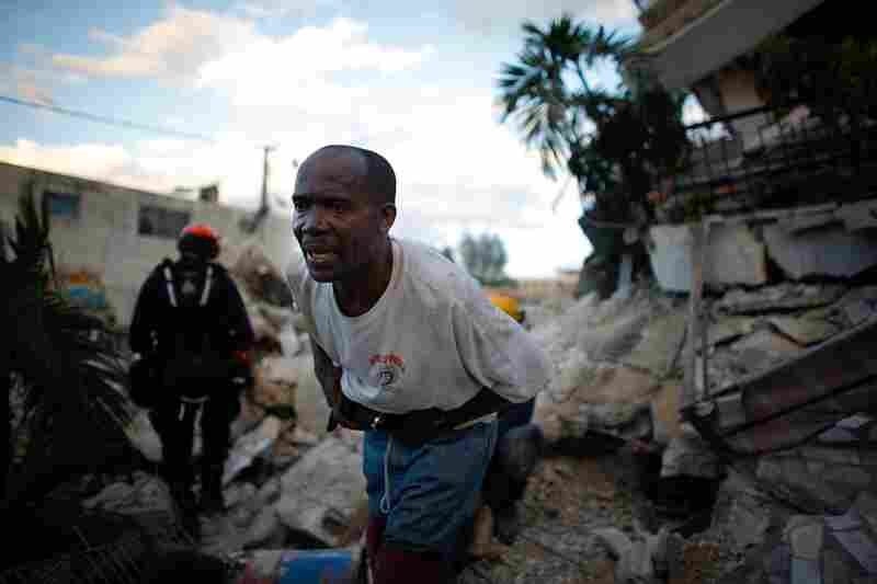 The search for people in the rubble continues. A Haitian rescue worker helps the L.A. County Search and Rescue team in in downtown Port-au-Prince.