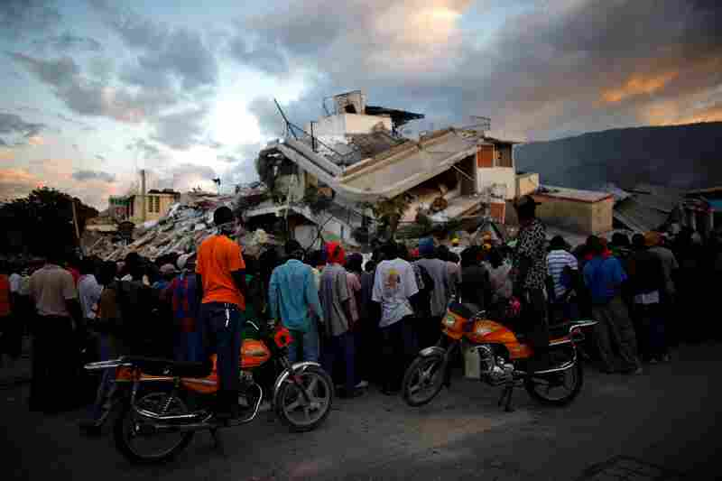 Haitians watch the L.A. rescue team's efforts at a collapsed building. Officials estimate at least 50,000 people were killed by the quake.
