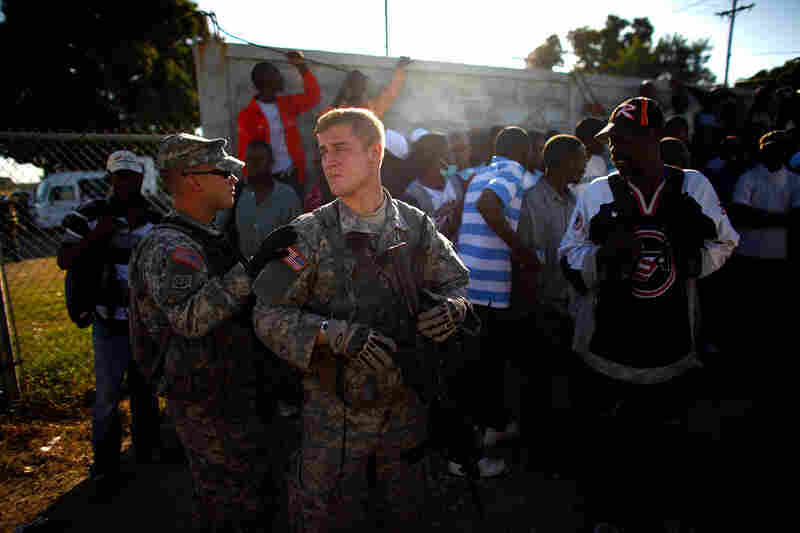 First Lt. Greg Bitner watches over Haitian men who have gathered at the airport in hopes of getting work.