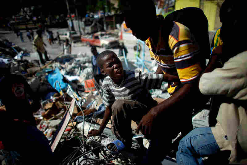 A boy tries to get a drink as looters scavenge the rubble of a supermarket Saturday in Port-au-Prince.