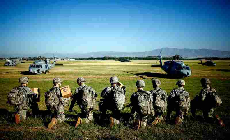 Soldiers with the U.S. Army's 82nd Airborne Division prepare to board helicopters to create operating bases across Port-au-Prince on Monday.