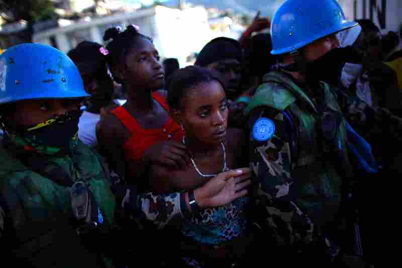Women stand in line for food rations being handed out by the United Nations Friday in Port-au-Prince.