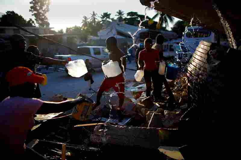 People gather around broken water pipes to collect fresh drinking water Friday in Port-au-Prince.