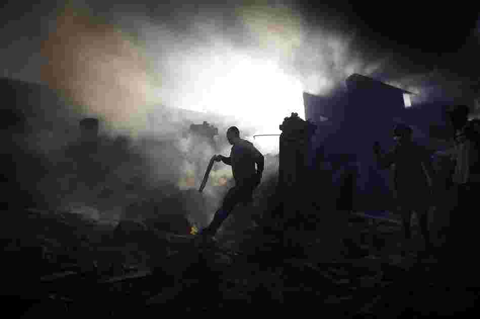 A man carries a shotgun as he walks through a collapsed burning building while trying to keep looters at bay on the streets outside in the commercial district of downtown Port-au-Prince.