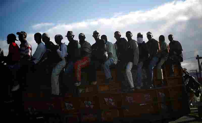 Men ride on the back of a truck leaving Port-au-Prince. U.N. officials warned that Haitians are becoming increasingly fed up with the pace of aid.