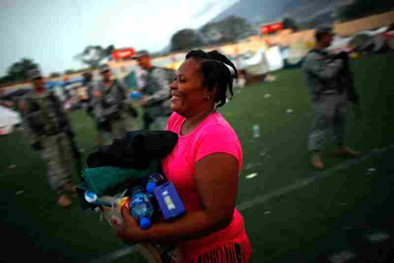 A Haitian woman receives her first ration of foreign aid in a soccer stadium in Port-au-Prince on Saturday.