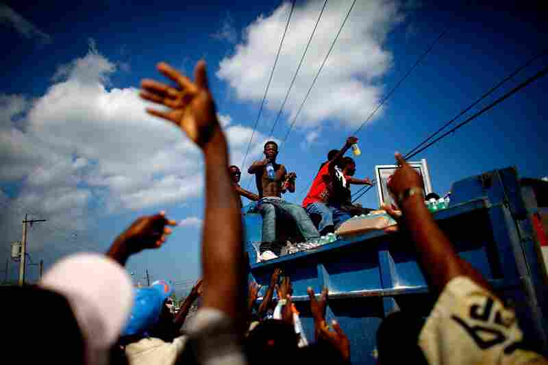 As survivors await international aid Sunday, Haitian men pass out water and soda taken from a collapsed store near Port-au-Prince.