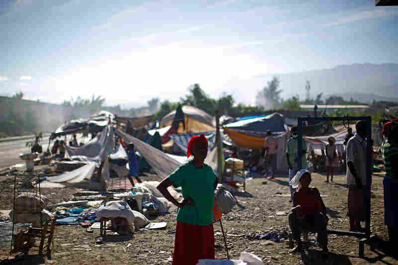 Refugees wait in a makeshift camp Saturday near downtown Port-au-Prince.