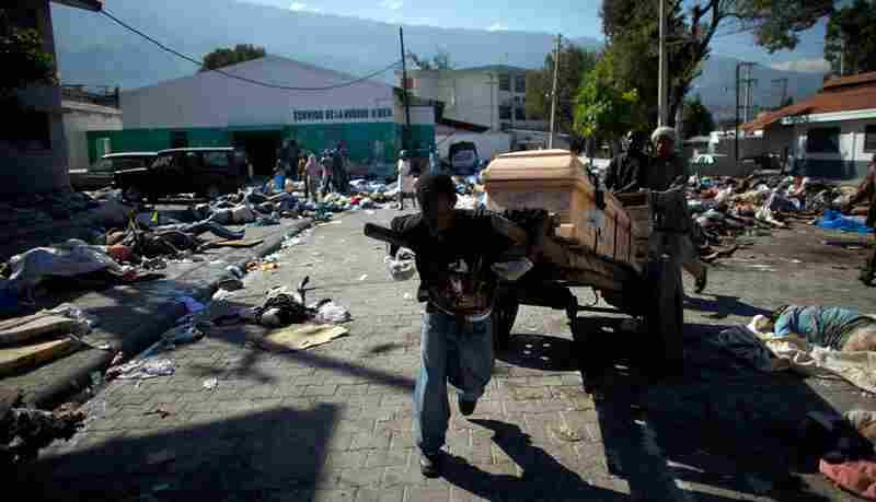 Men run with a casket after locating a family member's body among the hundreds strewn in the streets outside the National Hospital in Port-au-Prince.