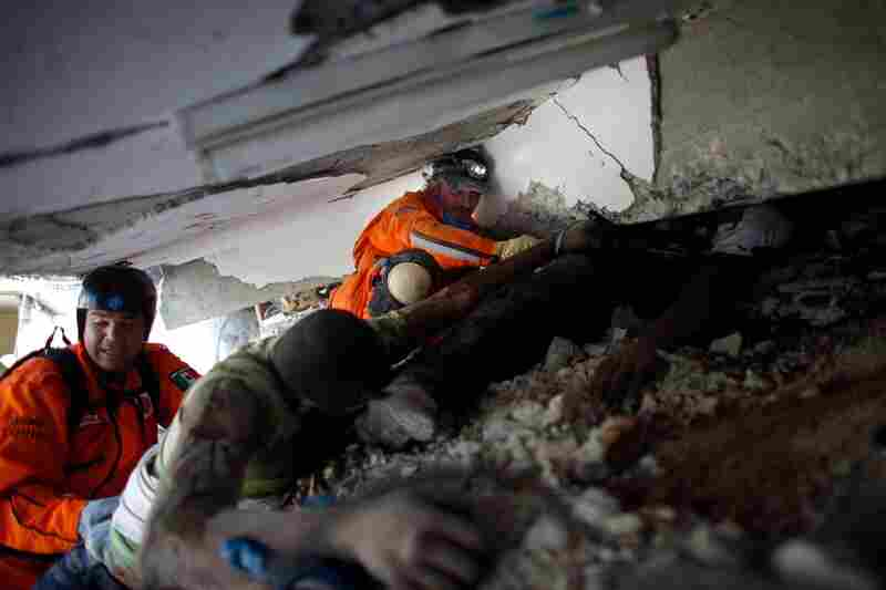 Mexican rescue workers try to extract the bodies of victims crushed during the collapse of the St. Gerard school outside of Port-au-Prince.