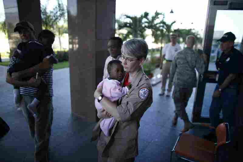 Melinda Pethel, a medical technician with the Georgia disaster assistance team, carries a baby into the American Embassy in Port-a-Prince on Monday. The baby arrived with a group from a Haitian orphanage.