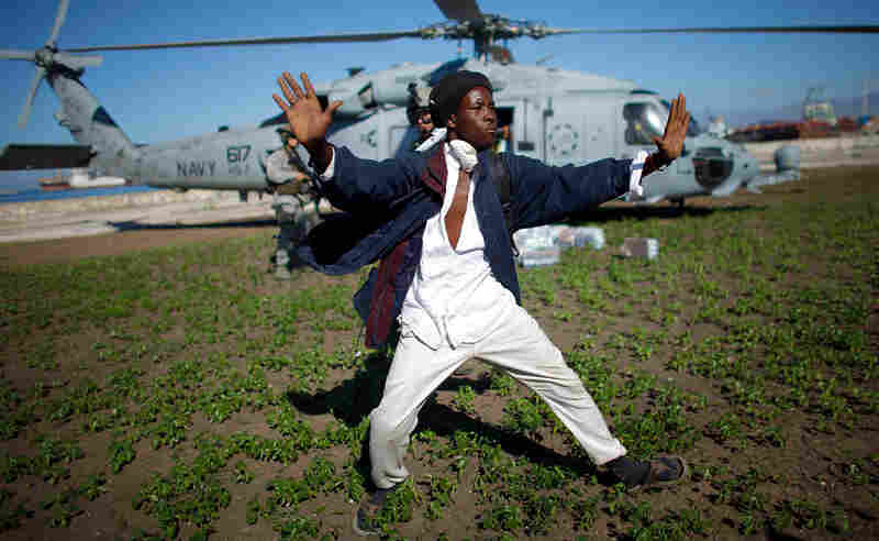 A Haitian man tries to keep a crowd from rushing a U.S. Navy helicopter as it unloads water in a Port-au-Prince park.