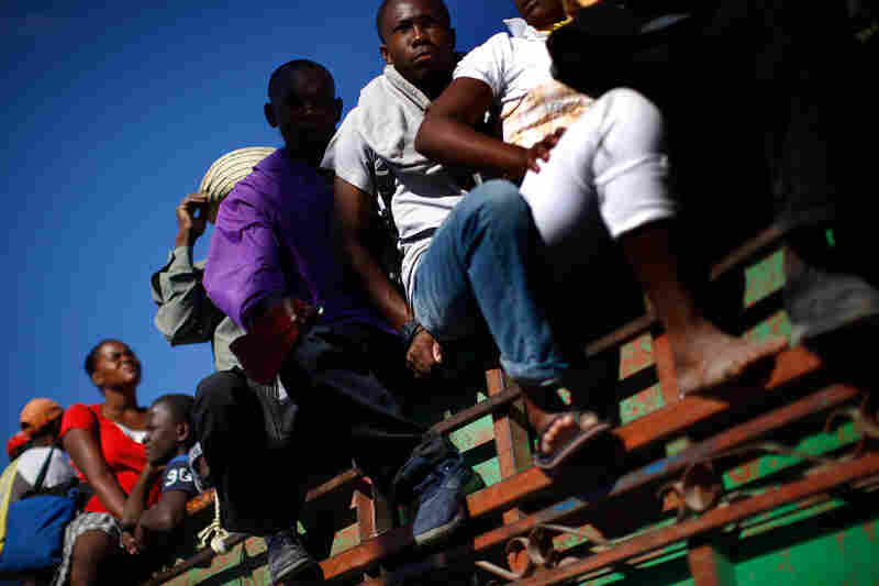 Haitians leave Port-au-Prince on a flatbed truck. Other towns in Haiti were also hit hard, but not much aid has made it beyond the devastated capital.