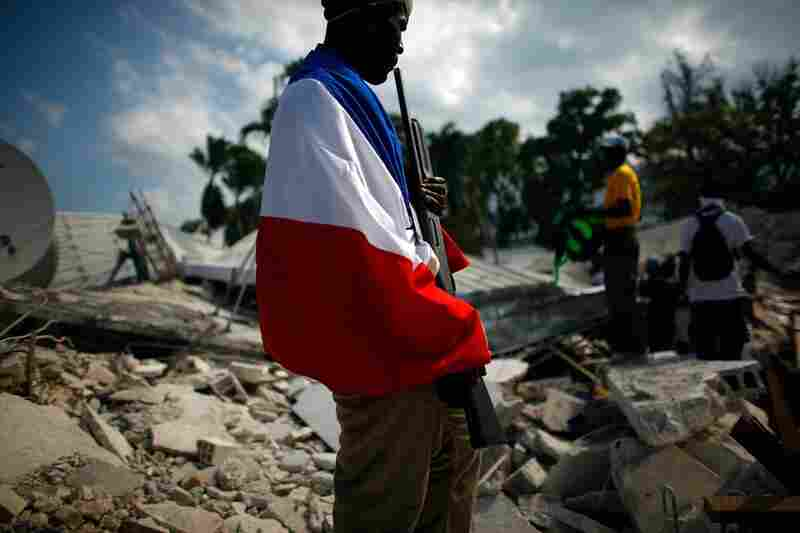 A Haitian man, draped in a French flag, guards a government building with a shotgun near the Port-au-Prince waterfront.