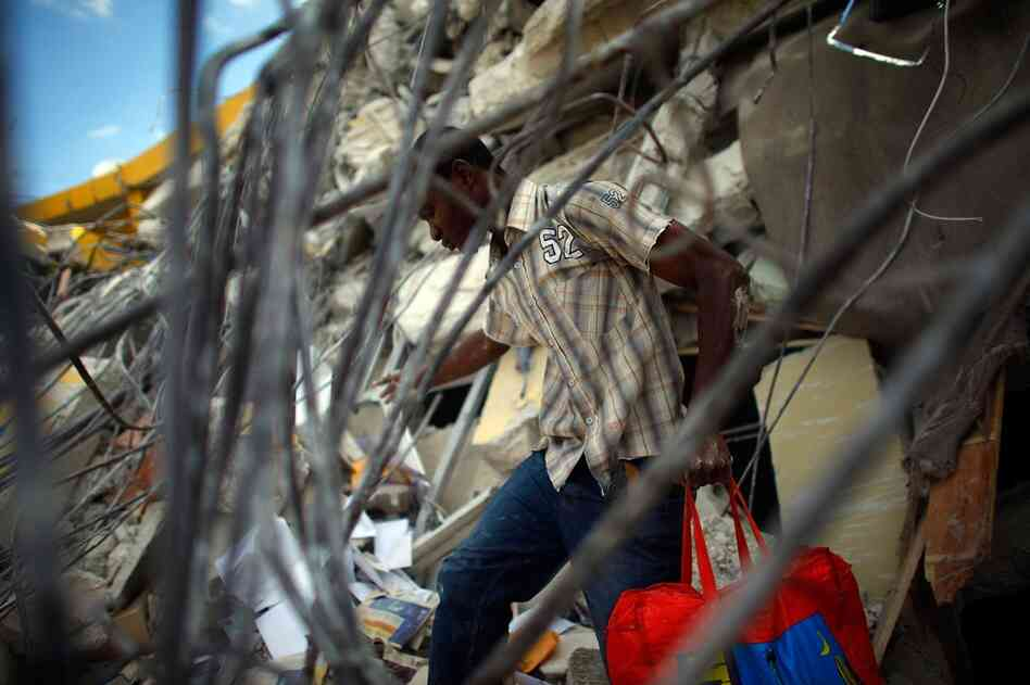 A Haitian man removes a bundle of goods from a collapsed store near Port-au-Prince.