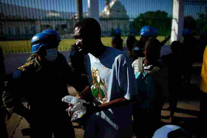 United Nations soldiers hand out water in front of the National Palace on Sunday.