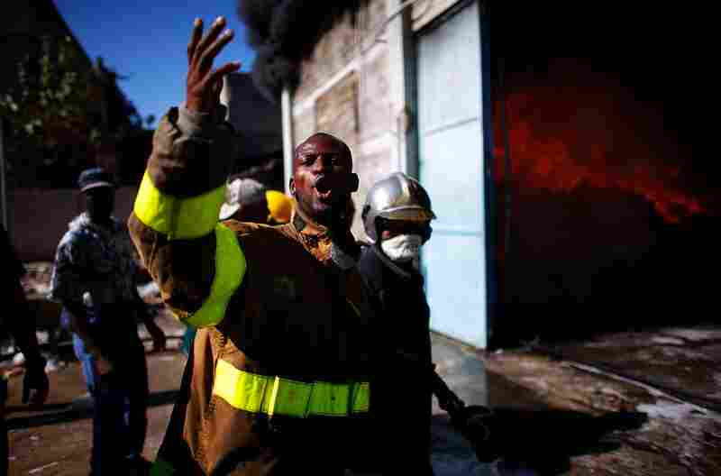 Firefighters yell for help as they try to put out a fire at the Pasta Mamma noodle factory in Port-au-Prince on Monday.