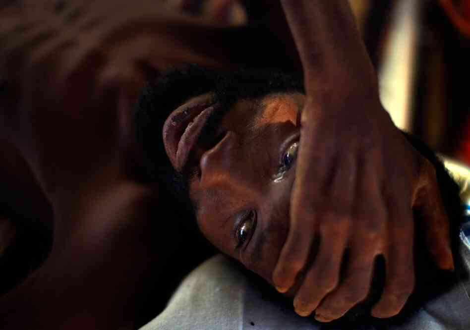 Robenson Bernard cries at a hospital in downtown Port-au-Prince on Monday. Bedridden since November, none of the family members who used to take care of him have come since the quake.