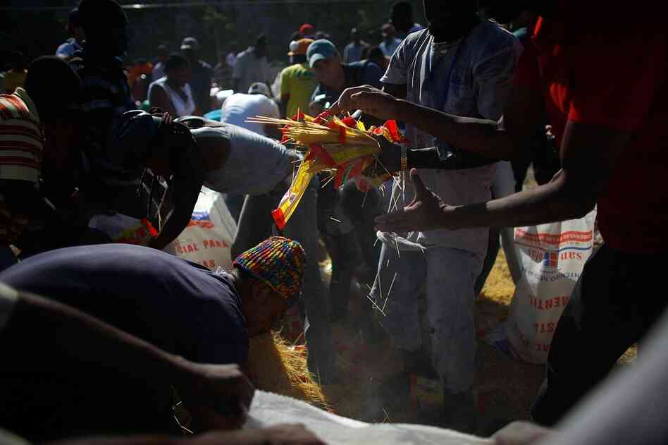 People scramble to pick up spilled spaghetti at the burning restaurant. With food supplies already low, the fire is yet another blow to a desperate capital.