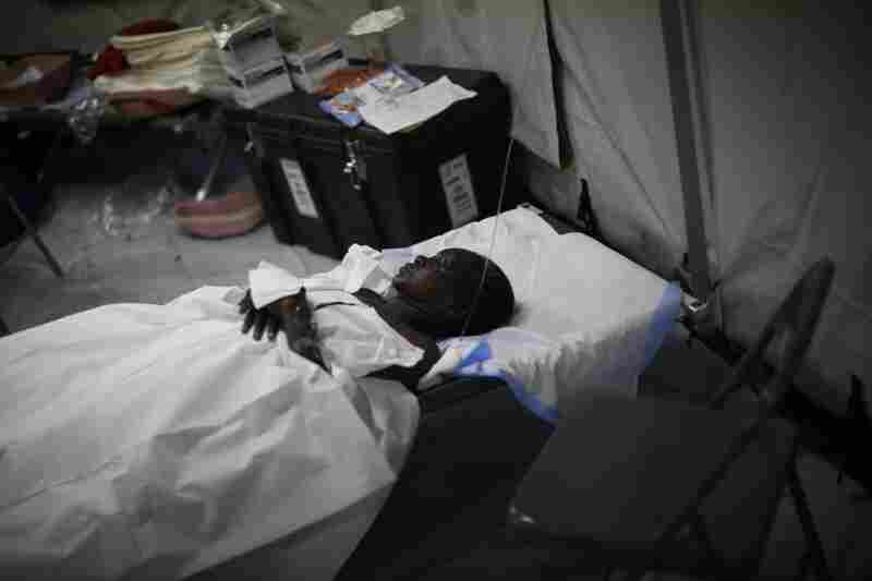 A patient sleeps in one of the medical tents. Thousands of people are waiting outside the clinic for medical and surgical treatment.