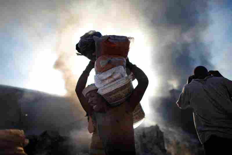 A man carries cloth from a shack behind a burning building in the commercial district of Port-au-Prince on Monday.
