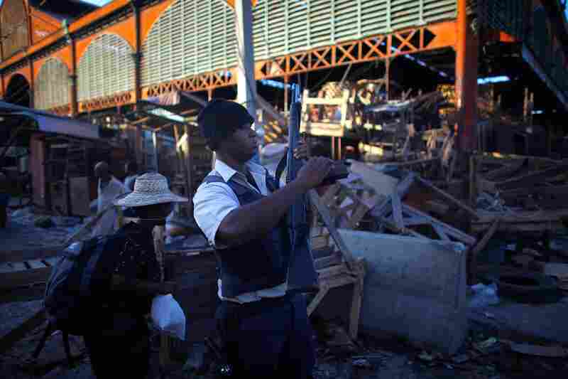 A Haitian policeman looks for looters approaching the commercial district of downtown Port-au-Prince.