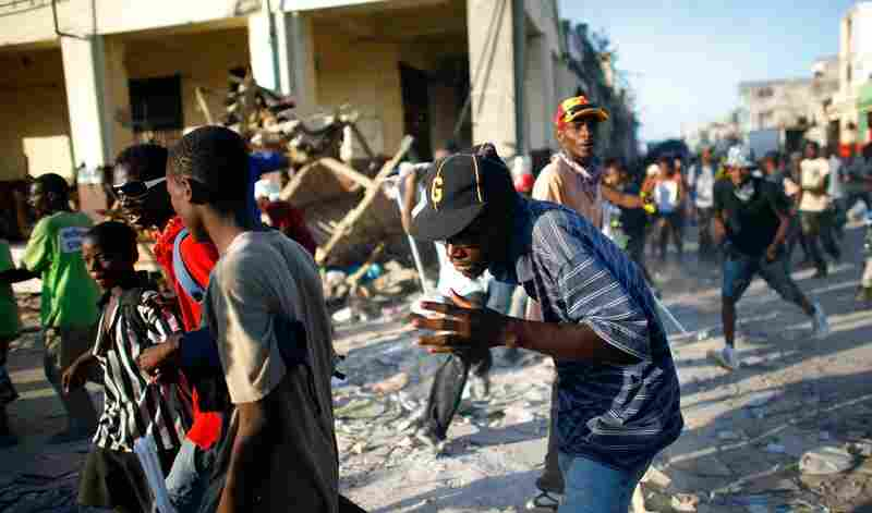 Haitians scatter as police fire shots in an attempt to disperse looters Monday in the commercial district of downtown Port-au-Prince.