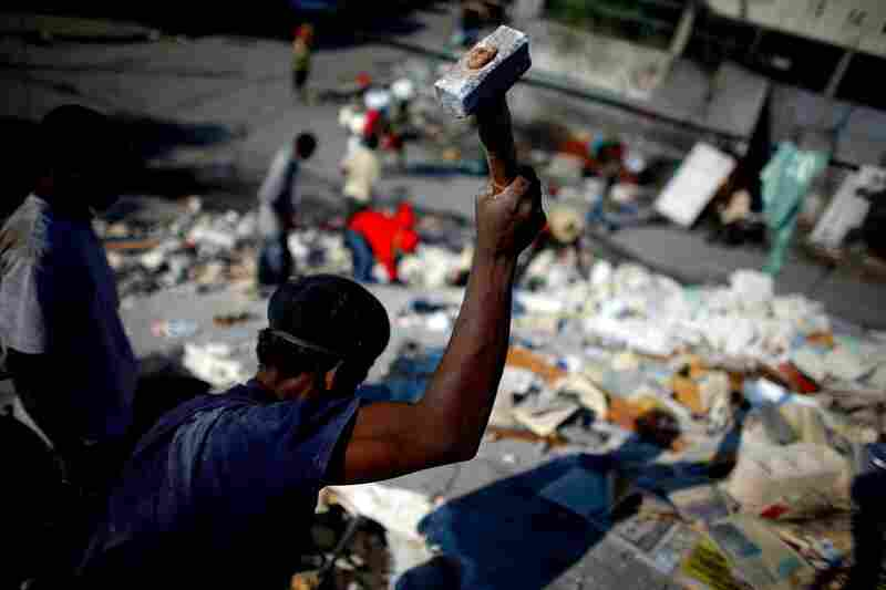 A Haitian man tries to hammer a hole through the roof of a collapsed home to reach trapped bodies Monday in Port-au-Prince.