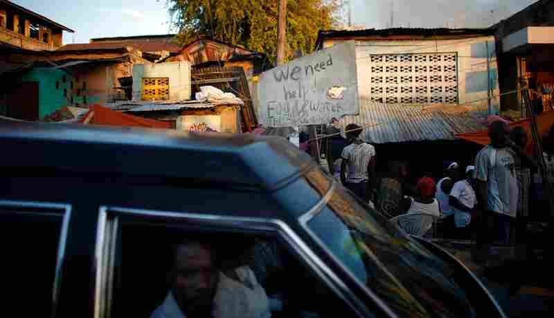 A hearse drives past a sign pleading for help near downtown Port-au-Prince.